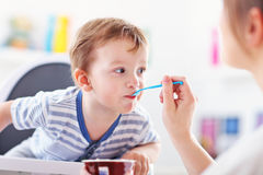 Mum spoon-feeds the child Royalty Free Stock Image