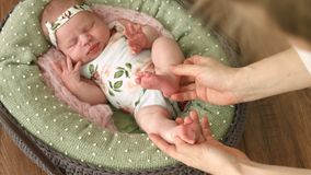 Mum strijkt de benen van haar pasgeboren dochter liggend in een mooi bed stock footage