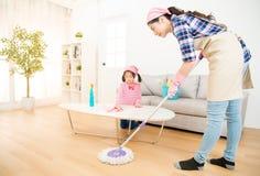 Mum teaching daughter cleaning home Stock Image