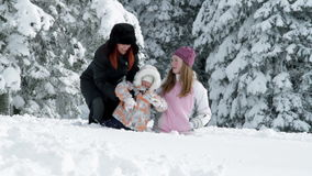 Mum, two girls enjoying on snow in winter. A young mother with two children while enjoying in the idyllic winter time soroundings stock video footage