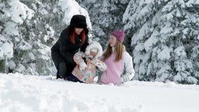 Mum, two girls enjoying on snow in winter stock video footage