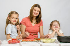 Mum with two little girls sitting at kitchen table preparing a pizza Royalty Free Stock Image