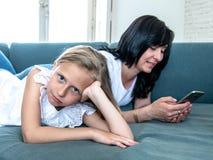 Mum viciado do Internet que usa seu telefone esperto que ignora sua criança só triste foto de stock