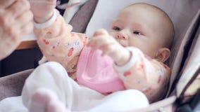 Mum voedt met een lepel haar leuke pasgeboren babypuree van courgetteclose-up stock video