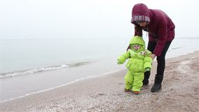 Mum walks with the child on a beach in winter.first steps stock video footage