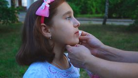 Mum wipes the child face with napkins. After a picnic in the nature in the park stock video