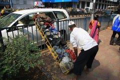 Mumbai/Índia - 24/11/14 - entrega de Dabbawala na estação de trem de Churchgate em Mumbai com o dabbawala que coloca o tiffin lev Foto de Stock