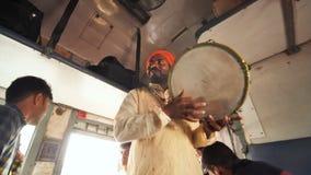 Mumbai, Ινδία - 17 Δεκεμβρίου 2018: Ο ινδικός μουσικός με ένα ντέφι τραγουδά στο τουριστικής θέσης αυτοκίνητο απόθεμα βίντεο