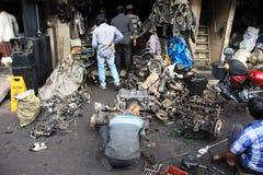 Mumbai/Inde - 22/11/14 - briseur de voiture démolissant une partie d'un moteur sur le marché de voleurs, Mumbai Photos stock