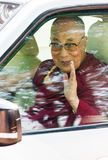 The 14th Dalai Lama inside a car, waving to people royalty free stock photos