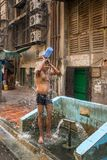 Indian man taking shower from bucket on streets of Mumbai, India. Mumbai, India - April 8, 2017: Indian man taking shower from bucket on streets of Mumbai, India Stock Image