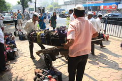 Mumbai/India - 24/11/14 - Dabbawala delivery at Churchgate Railway Station in Mumbai with two dabbawala's placing the tiffin carry Royalty Free Stock Images