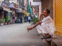 MUMBAI INDIA, GRUDZIEŃ, - 12, 2014: Mężczyzna opowiada na telefonie komórkowym z szczęśliwymi wyrażeniami przy jeden ulica Mumbai obraz royalty free