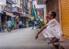 MUMBAI INDIA, GRUDZIEŃ, - 12, 2014: Mężczyzna opowiada na telefonie komórkowym z szczęśliwymi wyrażeniami przy jeden ulica Mumbai zdjęcia stock