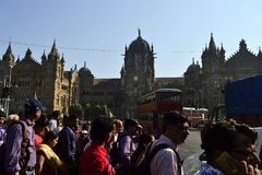 Crowd of people crossing street on background of Chhatrapati Shivaji Terminus railway station. Mumbai, India - January, 2017: Crowd of people crossing street on Stock Image