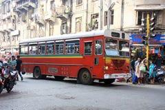 Mumbai/Indien - 22/11/14 - gammal röd retro bussresande till och med gatorna av Mumbai på den dagliga pendlingssträckan Arkivfoto