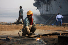 Mumbai/Indien - 23/11/14 - versenden den Unterbrecher-Schneidbrenner, der Teil INS Vikrant in Darukhana-Abwrackwerft demoliert Lizenzfreie Stockbilder