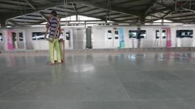 Mumbai Metro train at station and commuters waiting, entering the metro. MUMBAI, INDIA:August 29th 2014:Mumbai Metro train at station and commuters waiting stock video footage