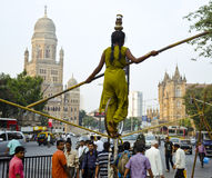 Acrobat Performing On-street Rope-Walk. Mumbai, state of Maharashtra, India- Dec 7, 2012. This is a scene of an acrobatic performance on the street in Mumbai Stock Photo