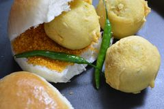 Mumbai Vada Pav. Famous Mumbai street food snack made with spicy potato filling in gram flour batter deep fried, eaten with Pav Indian bread stock photography