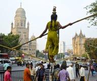 Akrobat, der Auf-Straße Seil-Weg durchführt Stockfoto