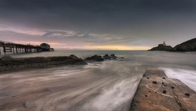 Mumbles pier and lighthouse. Dawn and a long exposure at high tide over Mumbles pier and Mumbles lighthouse in Swansea, South Wales, UK stock photo
