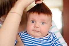 Mumen fäste eget hår till huvudet av nyfött och har gyckel Arkivfoton