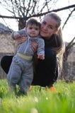 Mumen med barnet g?r p? gatan, l?r att g?, att studera v?rlden royaltyfri foto