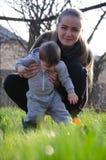 Mumen med barnet g?r p? gatan, l?r att g?, att studera v?rlden arkivbilder