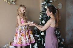Mumen med en dotter dekorerar julgranen som förbereder sig för jul, garnering, dekoren, livsstilen, familjen, familjevärderingar Arkivbilder
