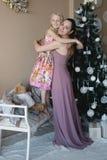 Mumen med en dotter dekorerar julgranen som förbereder sig för jul, garnering, dekoren, livsstilen, familjen, familjevärderingar Arkivbild