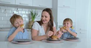 Mumen med två unga söner äter hamburgare hemma lager videofilmer