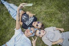 Mumen och söner som ligger i, parkerar på gräs ovanför sikt lycklig begreppsfamilj royaltyfri fotografi