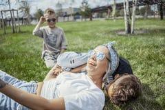 Mumen och söner som ligger i, parkerar på gräs ovanför sikt lycklig begreppsfamilj fotografering för bildbyråer