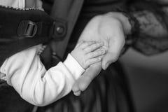 Mumen rymmer handen behandla som ett barn att sova i ett ergonomiskt behandla som ett barn bäraren Arkivfoton
