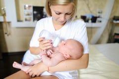 Mumen rymmer i armar, och matningar behandla som ett barn från flaskan, nyfödda drinkar mil Royaltyfria Bilder