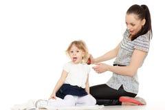 Mumen sköter hår av barnet. Arkivfoto