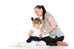 Mumen sköter hår av barnet. Royaltyfri Foto