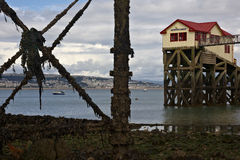 Mumlar den livfartyghuset och pir på lågvatten arkivfoton