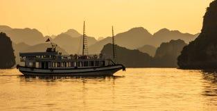 Mummel skäller länge öar, turist- fartyg och seascape i aftonen med den guld- ljusa reflexionen på vatten, mummel länge, Vietnam royaltyfri bild