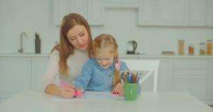 Mummia allegra e bambino occupati con il disegno a casa archivi video
