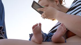 Mummia con il bambino addormentato alla spiaggia Donna che per mezzo del cellulare stock footage