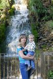 Mummia con il bambino vicino ad una cascata Fotografia Stock