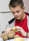 Mummia d'aiuto del ragazzo in cucina Fotografia Stock Libera da Diritti