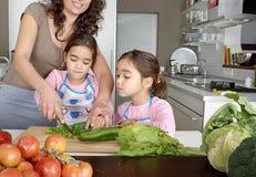 Mummia e figlia che tagliano le verdure a pezzi Fotografie Stock