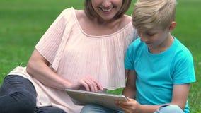 Mummia moderna e figlio che cercano informazioni in Internet, rete praticante il surfing, tecnologie archivi video