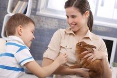 Mummia sorridente e piccolo figlio con il coniglio dell'animale domestico fotografie stock libere da diritti