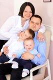 Mummy, daddy and two little sons indoors Stock Images