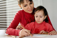 Mummy and daughter holding pencils Stock Images