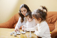 Mummy playing with daughters at home Stock Image